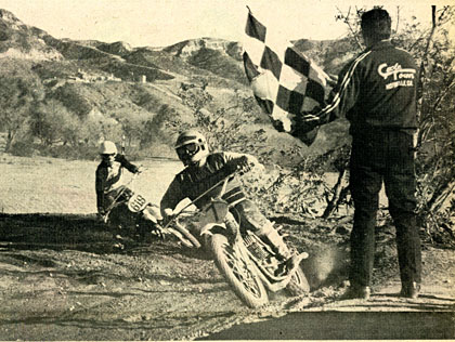 Super Hunky takes the checkered at the end of a long day of racing at Indian Dunes. Super is riding his famed square barrel Maico. Hatounian photo.